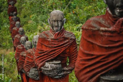 Leinwand Poster Old statues of Buddhist monks collecting alms surround the Win Sein Taw Ya Buddha in Mawlamyine, Myanmar (Burma)