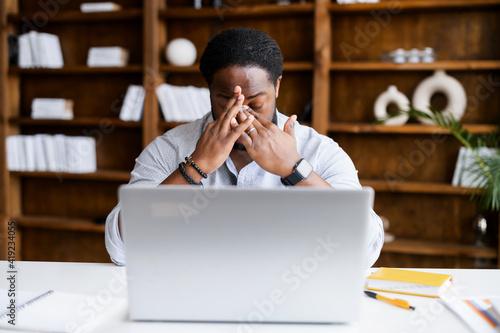 Fototapeta Overworked from online work on a laptop African-American man feeling eye strain,