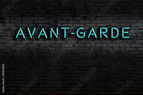 Fotografie, Obraz Neon sign. Word avant-garde against brick wall. Night view