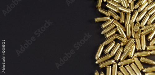 Fotografia Many brass gun bullets on black table closeup view from above, space for text le