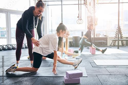 Obraz na płótnie Professional gym coach guiding women with stretching