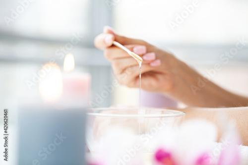 Photo Close up women hold orange paraffin wax bowl