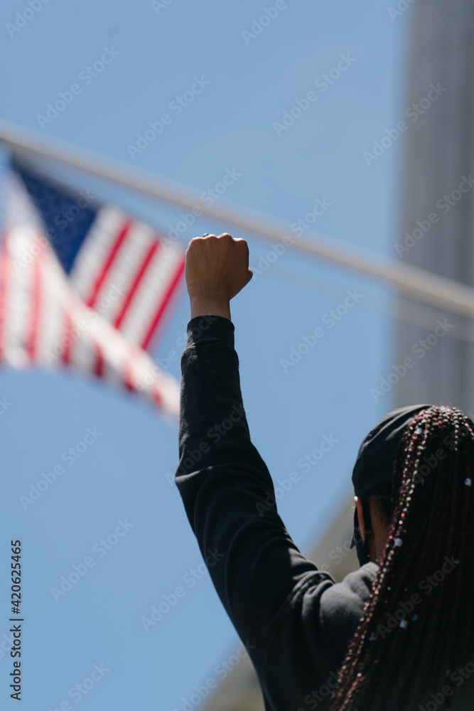 woman with her fist in the air in front of the American flag