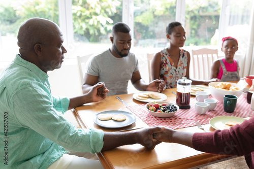 African american parents, daughter and grandparents sitting holding hands in prayer at dinner table