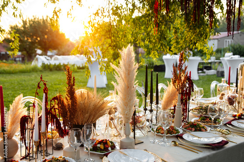 Fotografija Served outdoor banquet table with assorted oriental appetizers