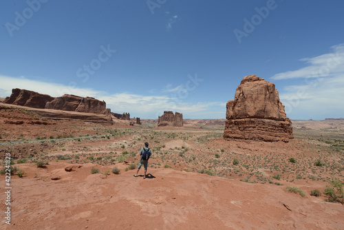 Photo A hiker looking at the vast landscape and red sandstone formations at Arches Nat
