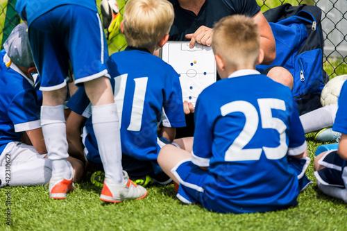 Fényképezés Sports coach teaching school boys on summer day