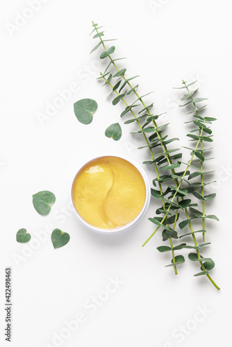 Fotografia Cosmetic gold eye patches in box on white background with eucalyptus branches