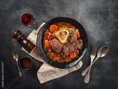 Fototapeta Italian menu: braised veal steak Ossobuco alla Milanese with  vegetable sauce close-up