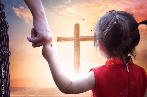 Fotografia Child's hand holding mother's finger on blurred The cross of jesus christ background
