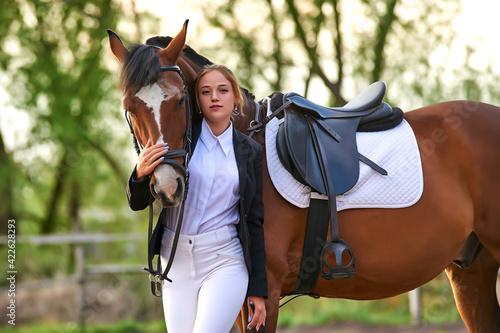 Beautiful horse rider girl stands near a horse on a farm Fototapeta