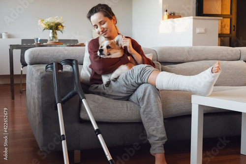 Adult woman in her late twenties on couch at home with crutches and orthopedic plaster caress the dog Fototapeta