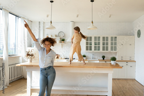 Overjoyed young Caucasian mother and little 8s daughter have fun dancing together in new renovated kitchen Fototapet