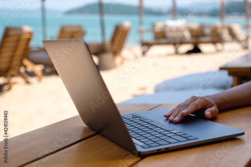 Obraz na plátně Closeup of a woman working and touching on laptop touchpad on the beach