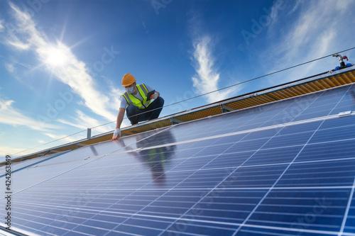 Obraz na płótnie technician checking the maintenance of the solar panels on roof, solar energy