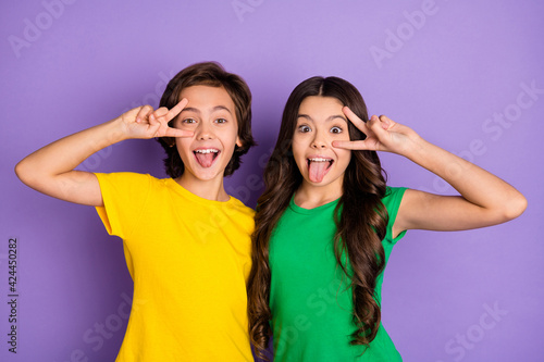 Obraz na płótnie Photo of two little boy and girl make funny face tongue out show v-sign isolated