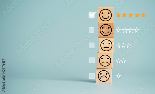 Photo Customer satisfaction survey concept, human face icons print screen on wooden cube block with stars and mark on blue background for evaluate product and service