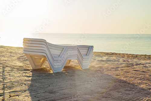 Foto Folded plastic deck chairs on a deserted beach by the sea