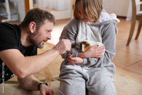 Fotografia Dad and daughter play with pet guinea pig