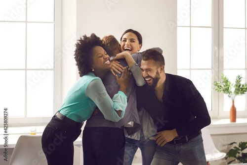 Tablou Canvas Group of overjoyed young diverse people hugging each other