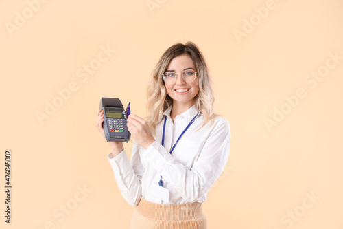 Fototapeta Young woman with payment terminal on color background