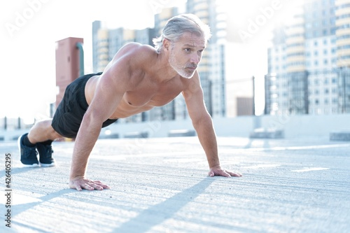 Middle-aged athletic man doing push ups outdoors. Fitness and exercising outdoors urban environment.