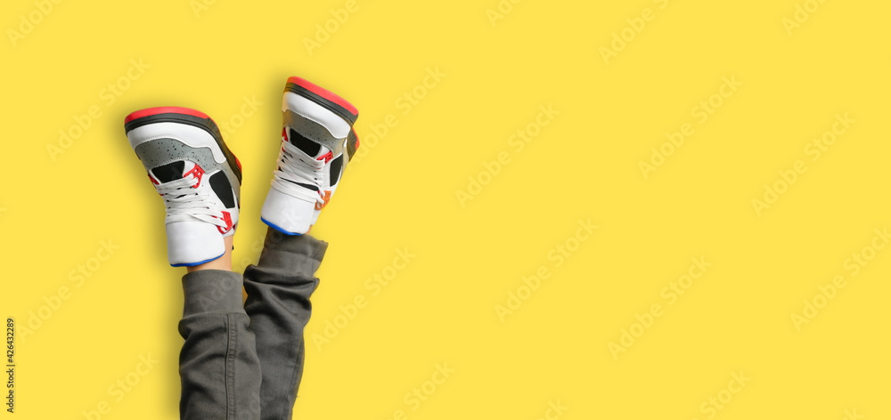 Close up of kids feet in a pair of colorful red sneakers isolated on yellow background. web border of sports and active leisure