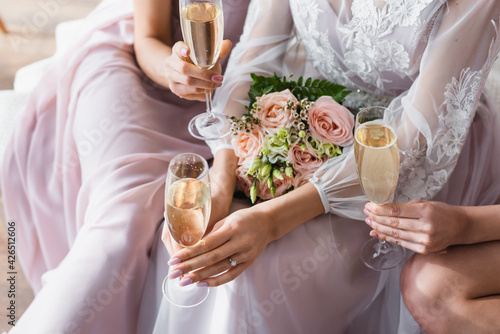 Fotografia cropped view of bride and wedding bouquet near bridesmaids with champagne glasses