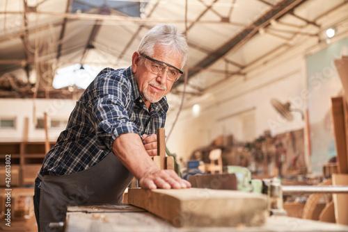Billede på lærred Craftsmen as carpenter master planing wood