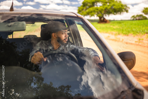 Fotografering Latin american farmer driving car