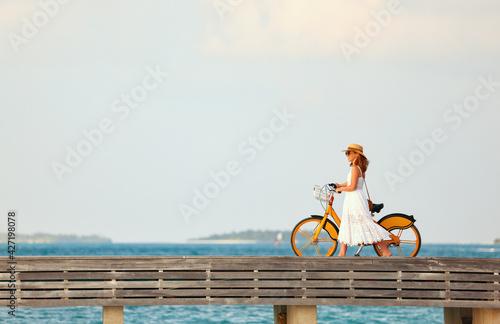 Fotografie, Obraz Woman walking with bicycle along promenade
