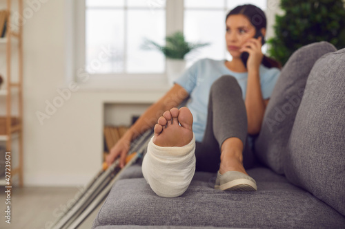 Photo Young woman with broken leg in cast lying relaxing on sofa with crutches nearby and talking on phone at home, selective focus