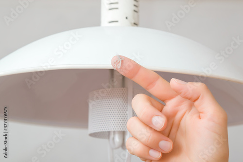 Fotografija Young adult woman finger showing dust from top of white lamp shade in room
