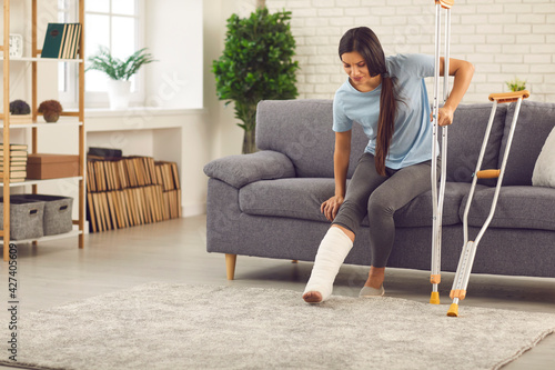 Fotografia Young smiling woman with broken leg in cast trying to stand up with crutches from sofa at home with room interior at background