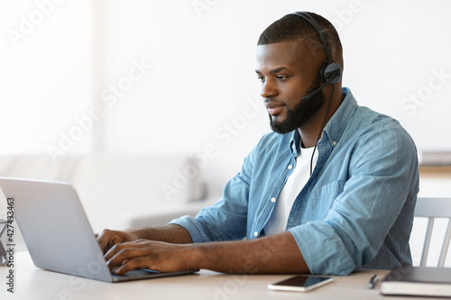 Fotomural Black millennial man in headset working remotely with laptop at home office