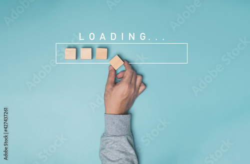 Fotografie, Obraz Hand putting wooden cube block with infographic for download on blue background , Technology and business progress concept
