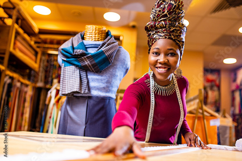 Canvas Print tanzanian woman with snake print turban over hear working in fabrics shop