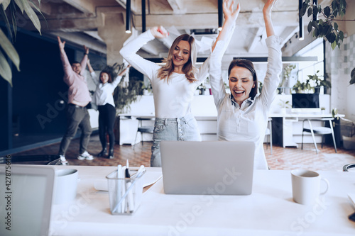 Two young happy businesswomen celebrating project success in office