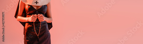 Fotografia cropped view of sexy nun in leather dress holding prayer beads isolated on pink,
