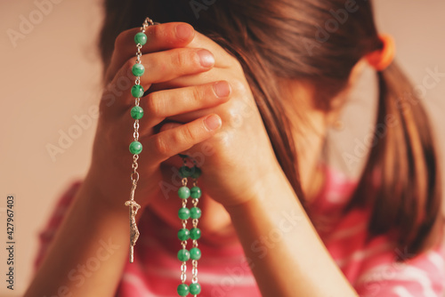 Fotografie, Obraz Young girl holding rosary and praying to God. Close up.