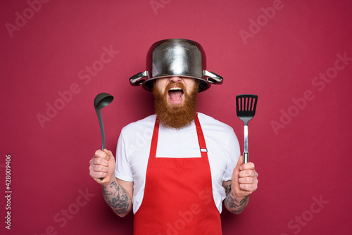 Wallpaper Mural Man chef is ready to fight in the kitchen. burgundies background