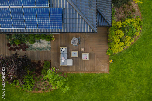 Fotografiet Top view of suburban house with green garden and wooden terrace