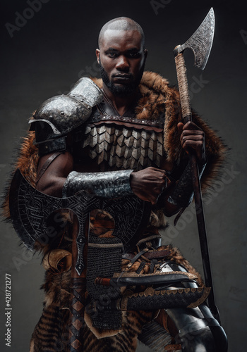 Fotografia, Obraz African guy dressed in military nordic costume holding an axe