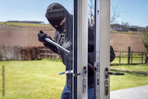 Obraz na plátně Burglar breaking into a house via a window with a crowbar