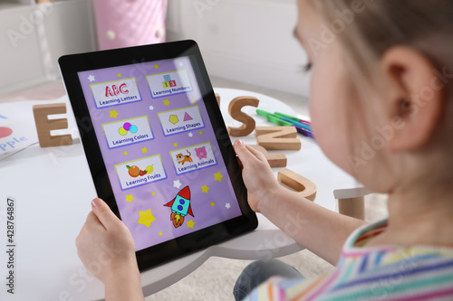 Carta da parati Little girl learning English with tablet indoors at online lesson, closeup