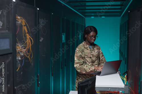 Wallpaper Mural Portrait of young African-American woman wearing military uniform using computer