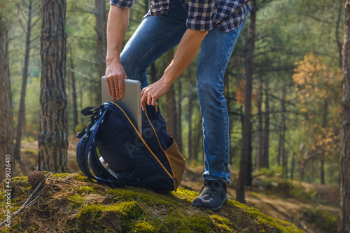 Fototapeta Cropped photography of young man getting laptop from the backpack at the forest