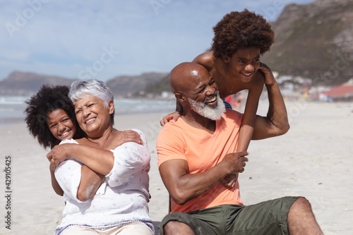 African american grandparents and grandchildren hugging while siting on the beach