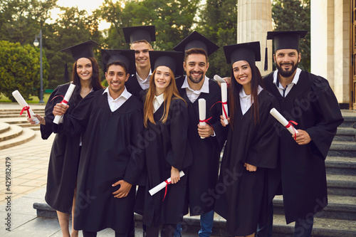 Group of graduate students in robes and mortarboards holding their diplomas near university campus Fototapet
