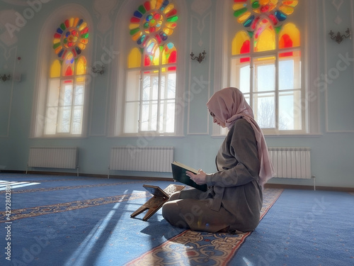Fotografia woman praying in the mosque and reading the Quran